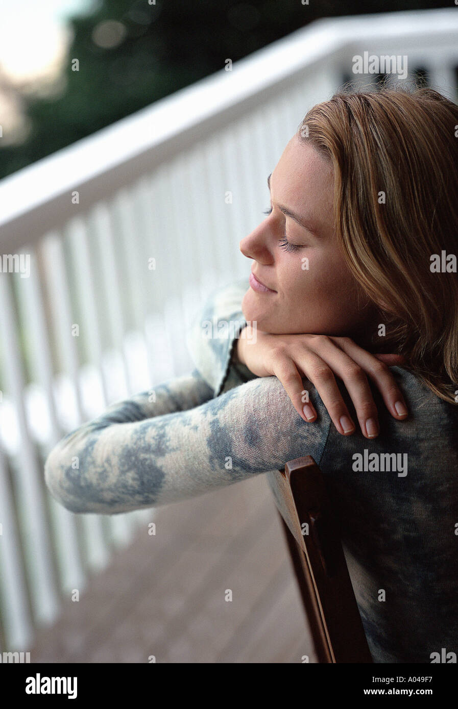 Young woman sitting on a chair relaxing - Stock Image