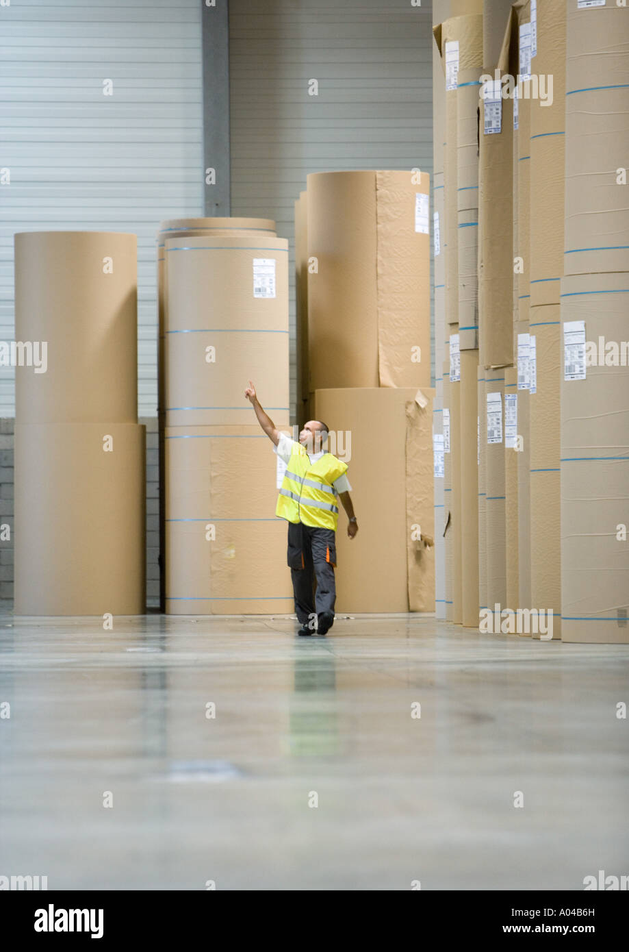 Factory worker standing next to rolls of paper, pointing - Stock Image