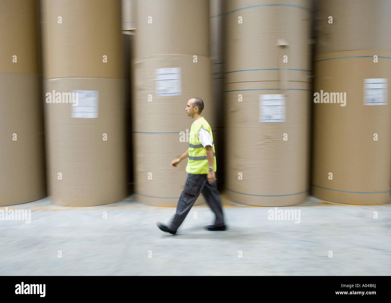 Factory worker walking past rolls of paper - Stock Image