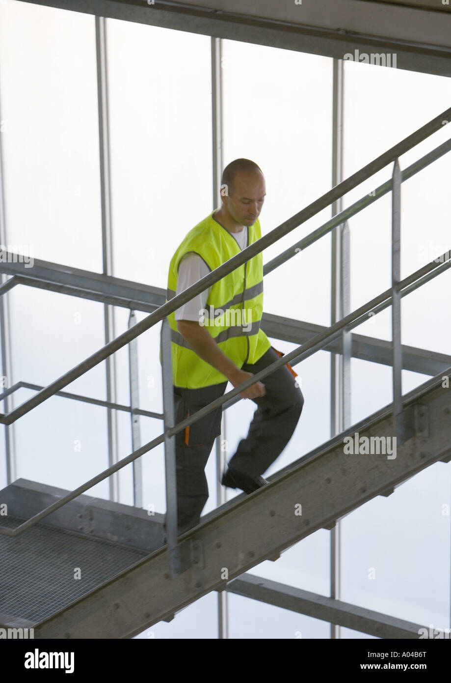 Factory worker walking up stairs - Stock Image