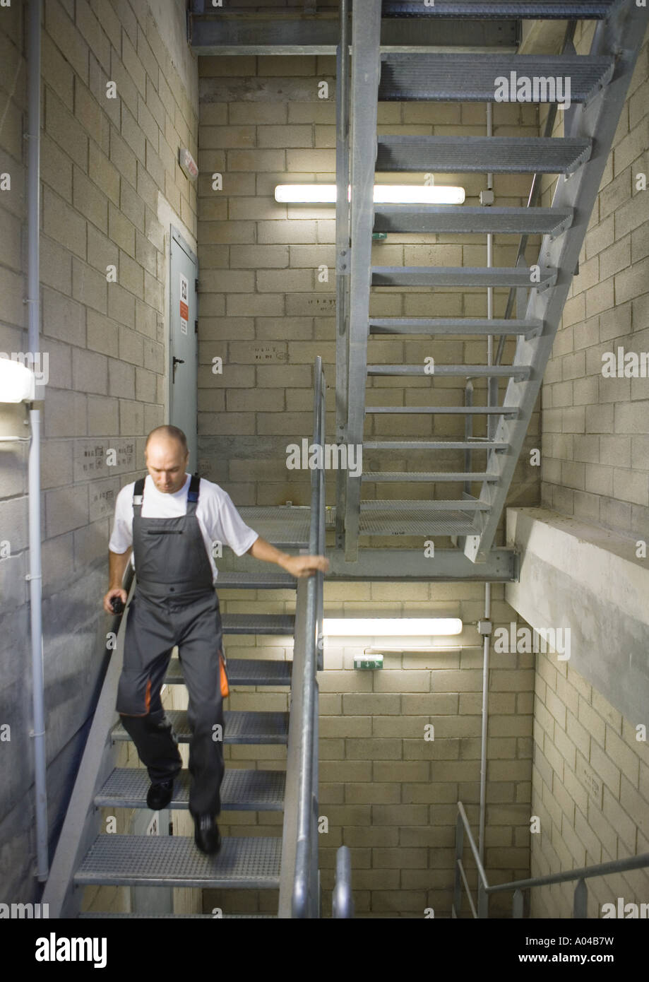 Factory worker walking down stairs - Stock Image