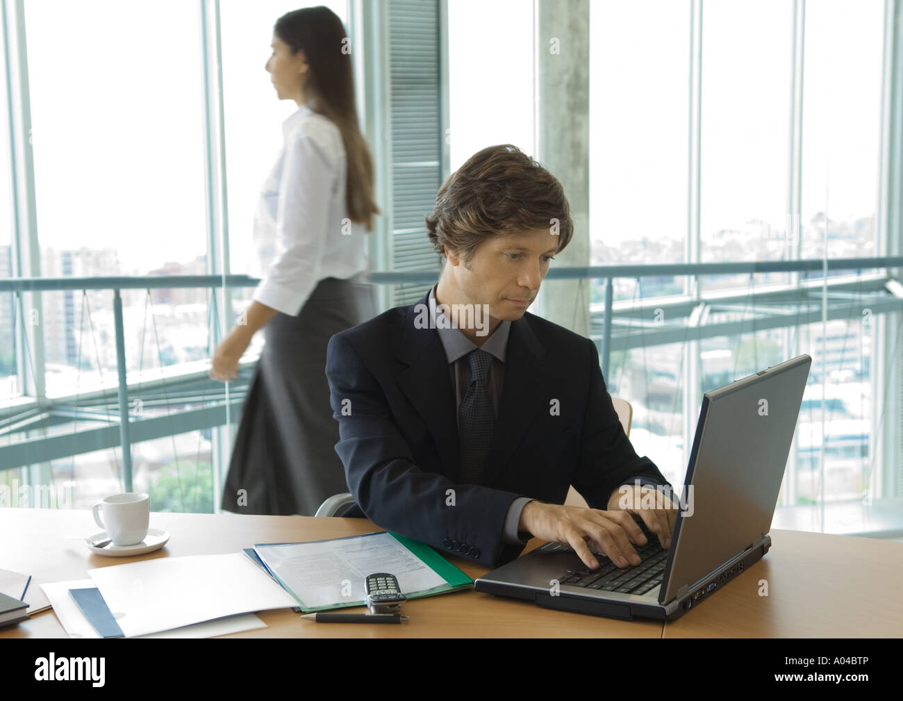 Businessman using laptop, woman walking by in background - Stock Image
