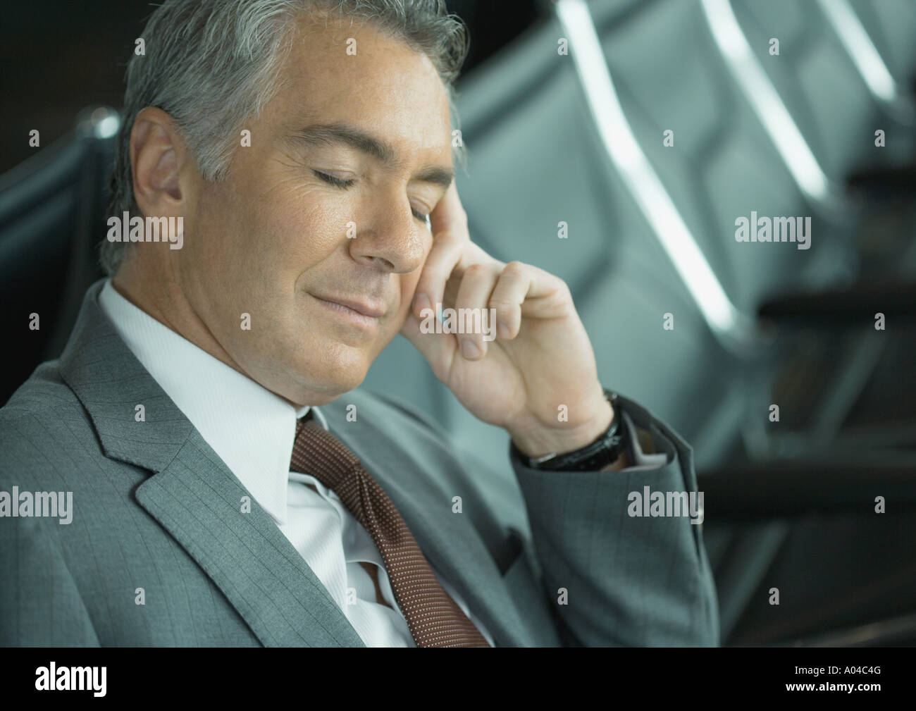 Businessman sleeping in airport lounge Stock Photo