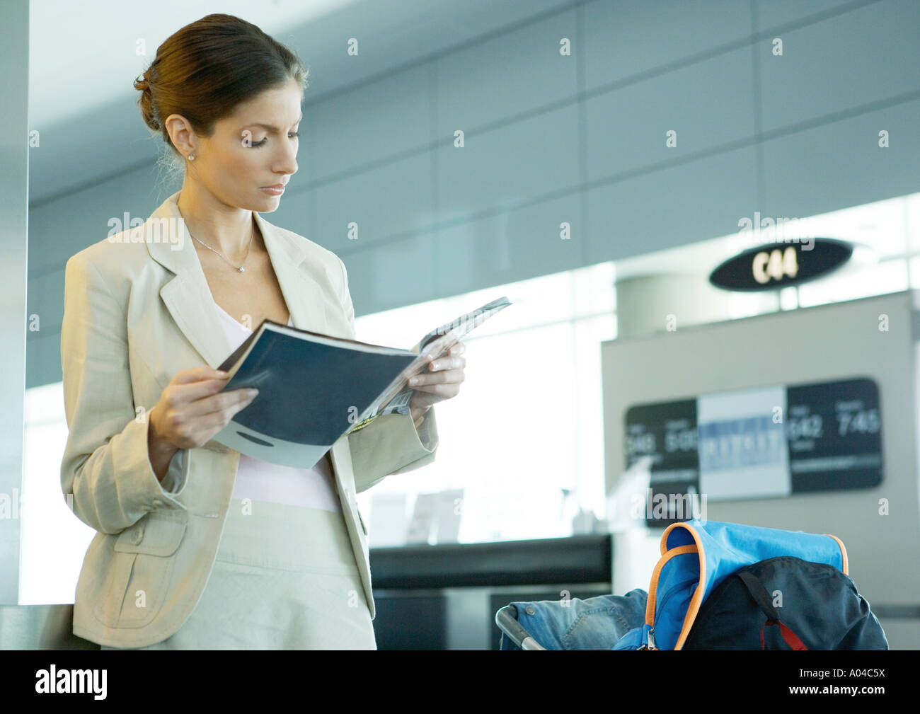 Woman standing in airport near departure gate - Stock Image