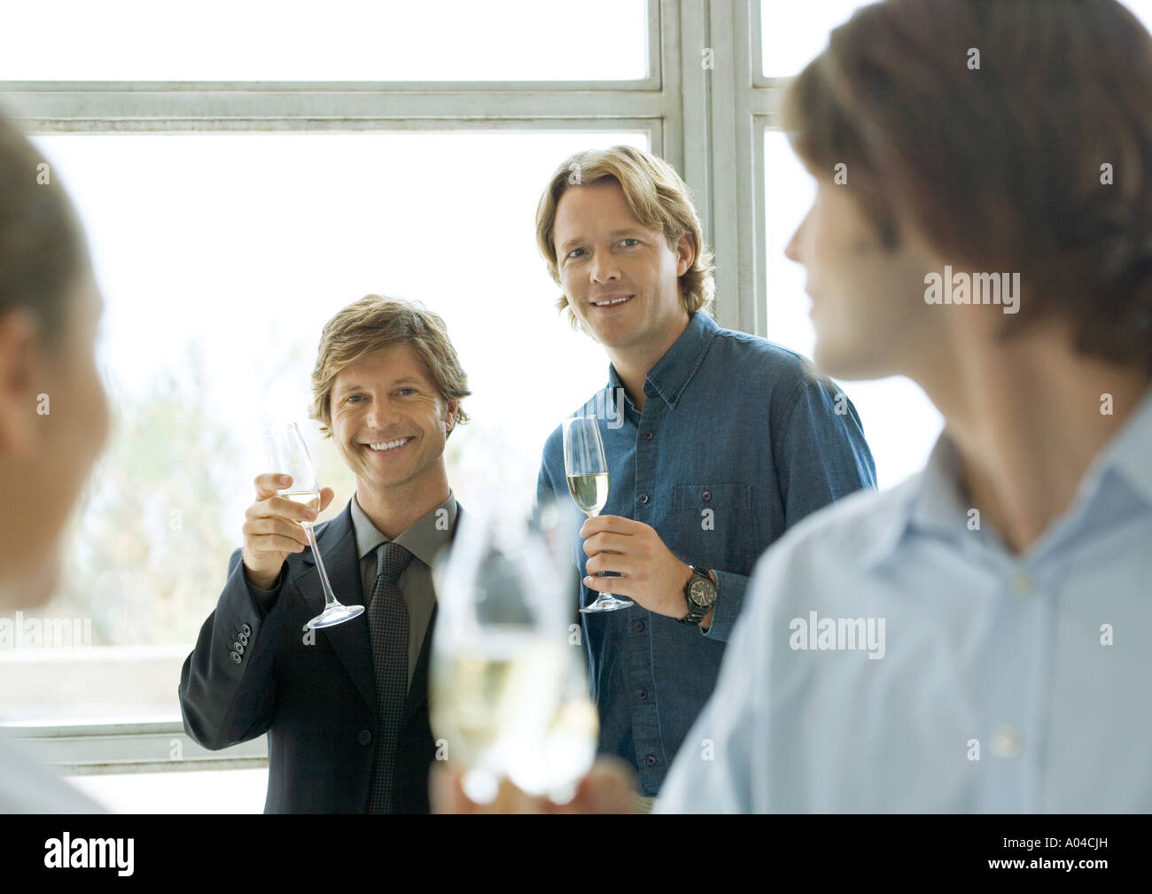 Men holding up glasses of champagne during cocktail party - Stock Image