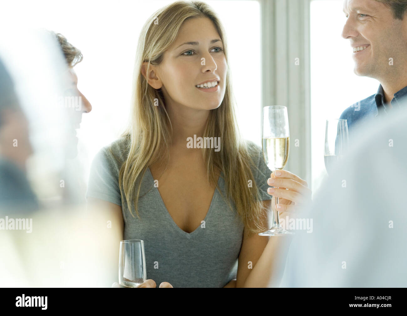 Woman holding glass of champagne during cocktail party - Stock Image