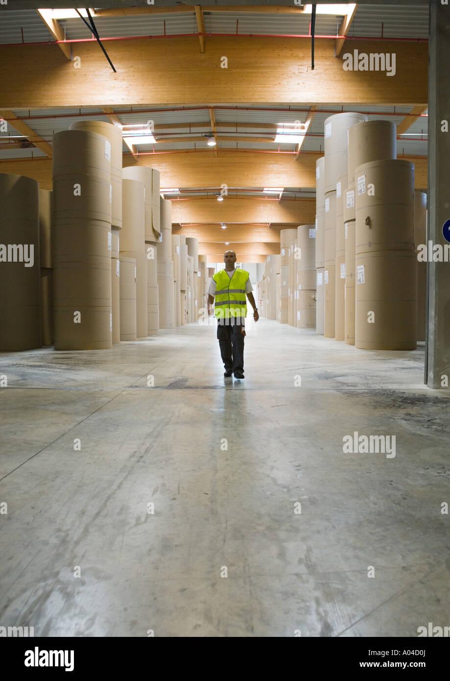 Man walking through rolls of paper in warehouse - Stock Image