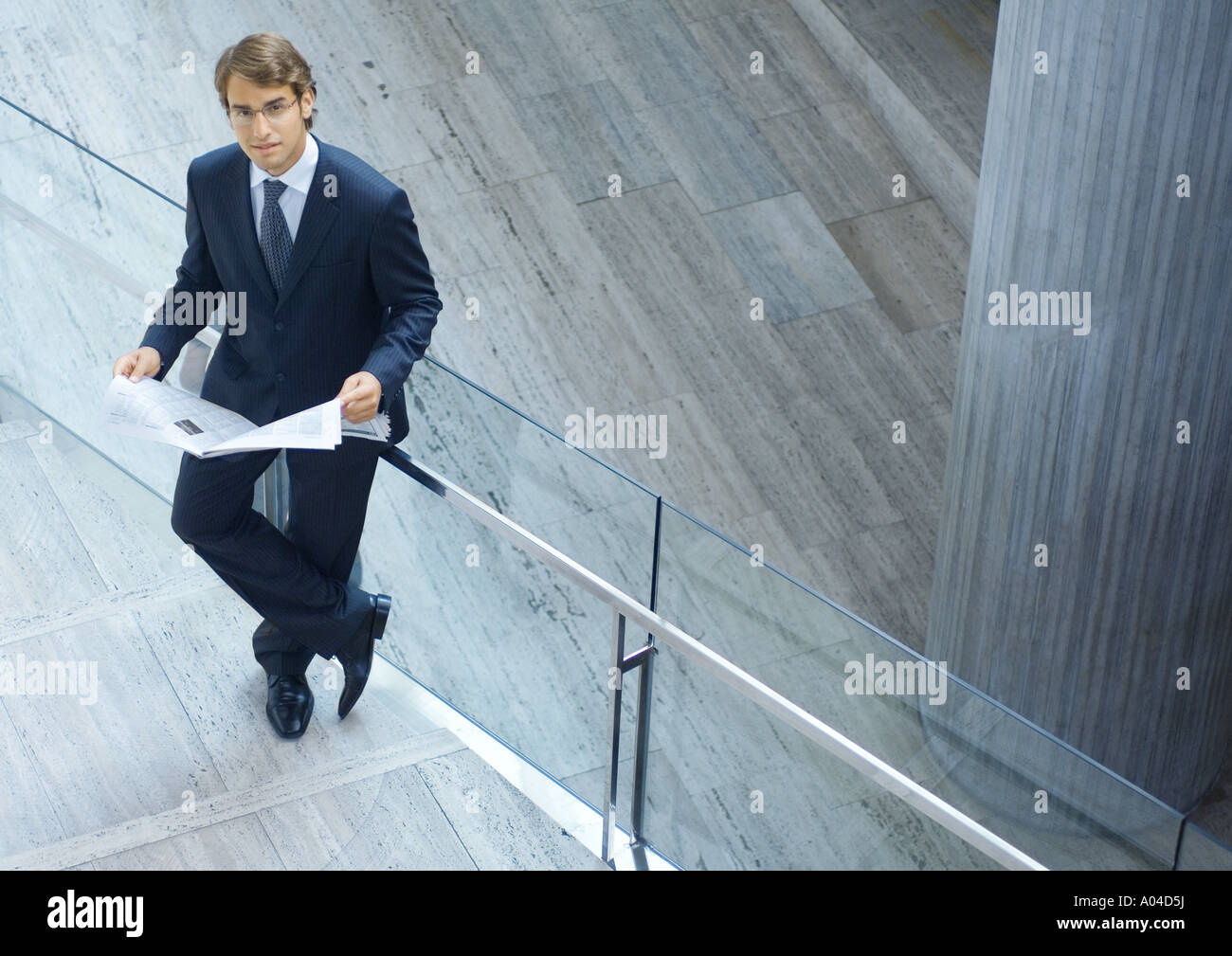 Businessman reading newspaper, high angle view - Stock Image