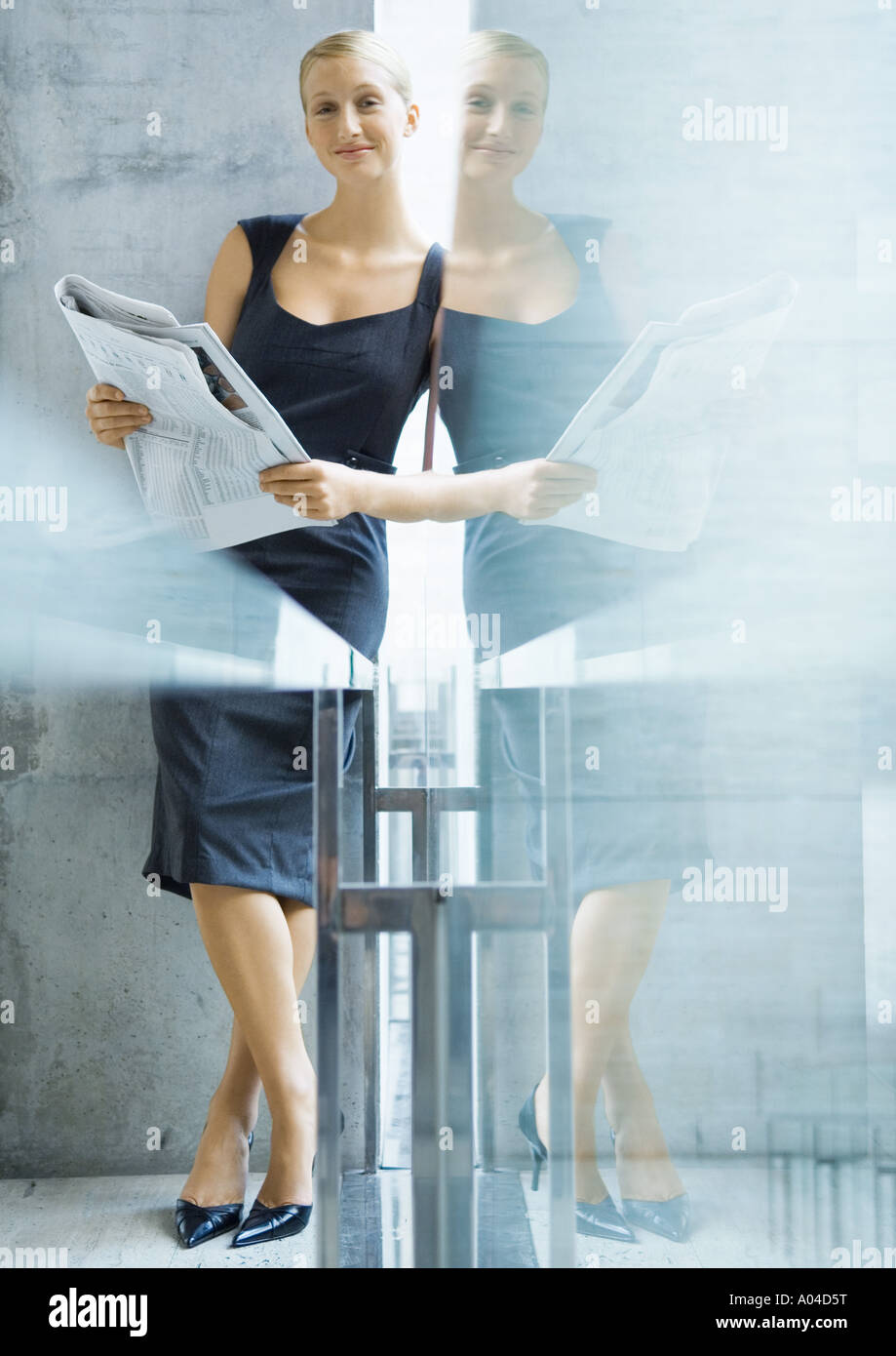 Businesswoman with newspaper, with reflection - Stock Image