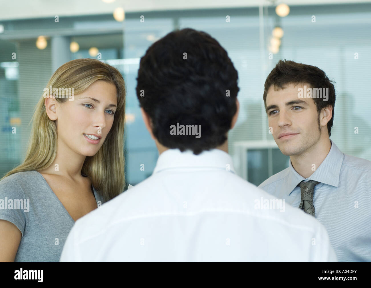 Two business associate speaking to man with back to camera - Stock Image