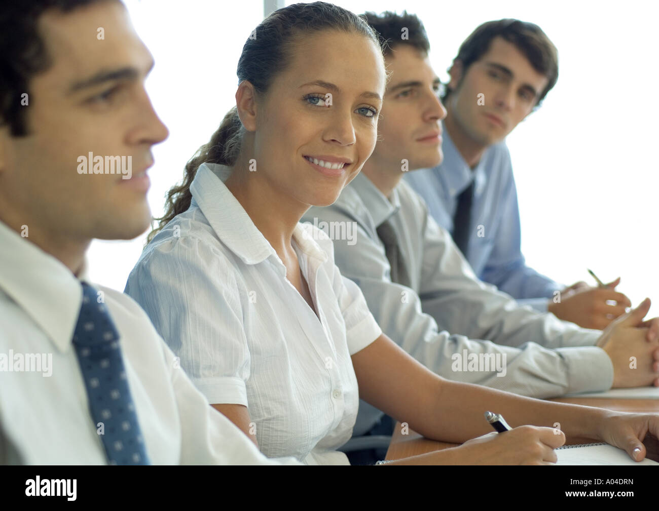 Business associates sitting at table, woman smiling at camera - Stock Image
