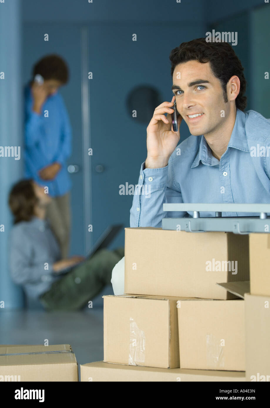 Young businessman using cellphone, sitting at table supported by cardboard boxes - Stock Image