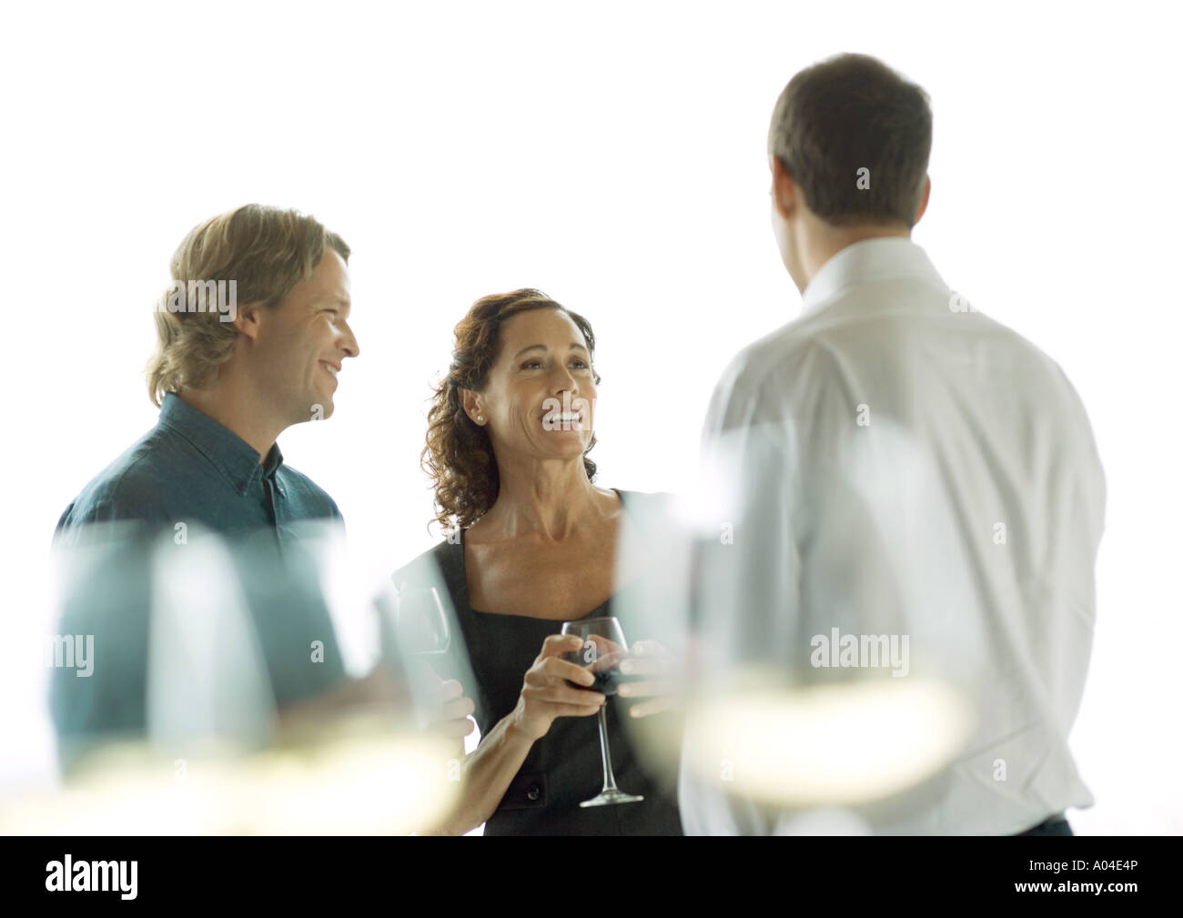 Three people chatting and drinking wine - Stock Image
