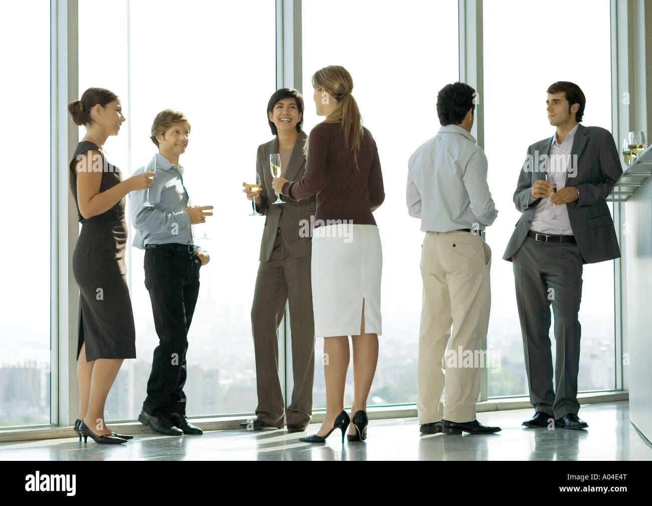 People standing with glasses during office party - Stock Image