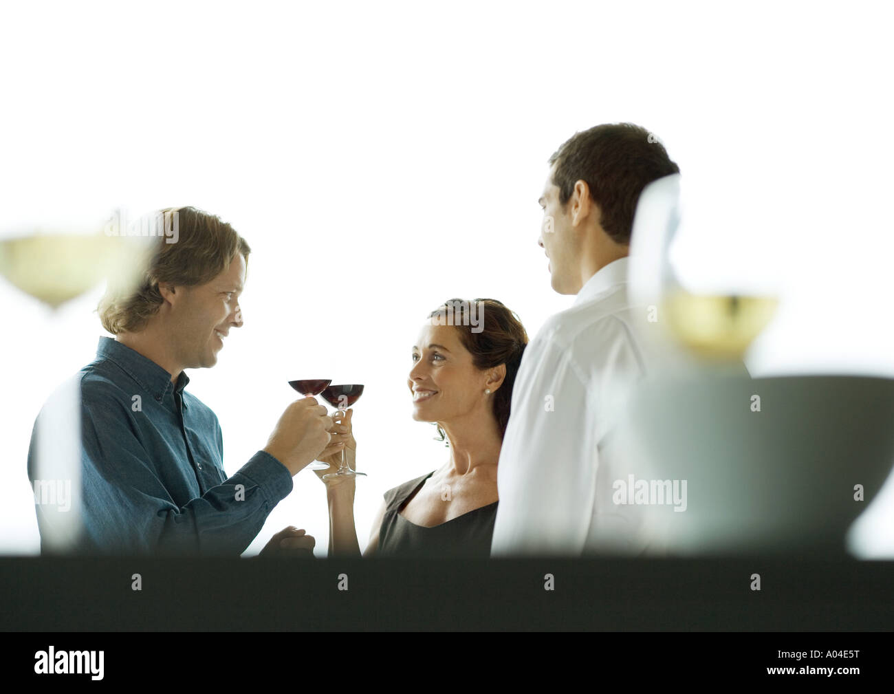 Man and woman clinking glasses during party Stock Photo