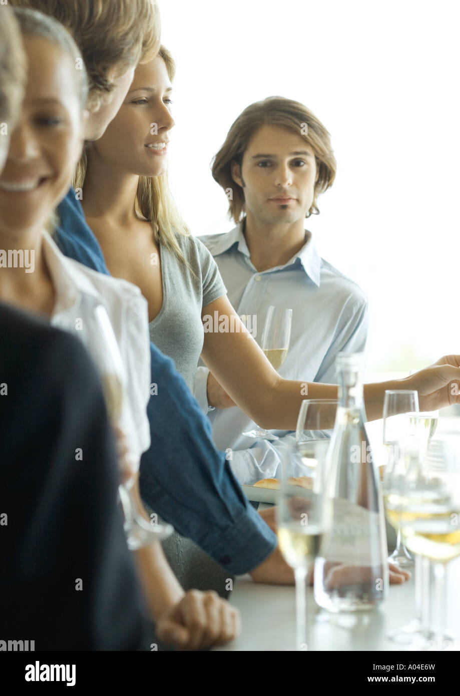 Group of young adults standing at bar, focus on man in background looking at camera - Stock Image