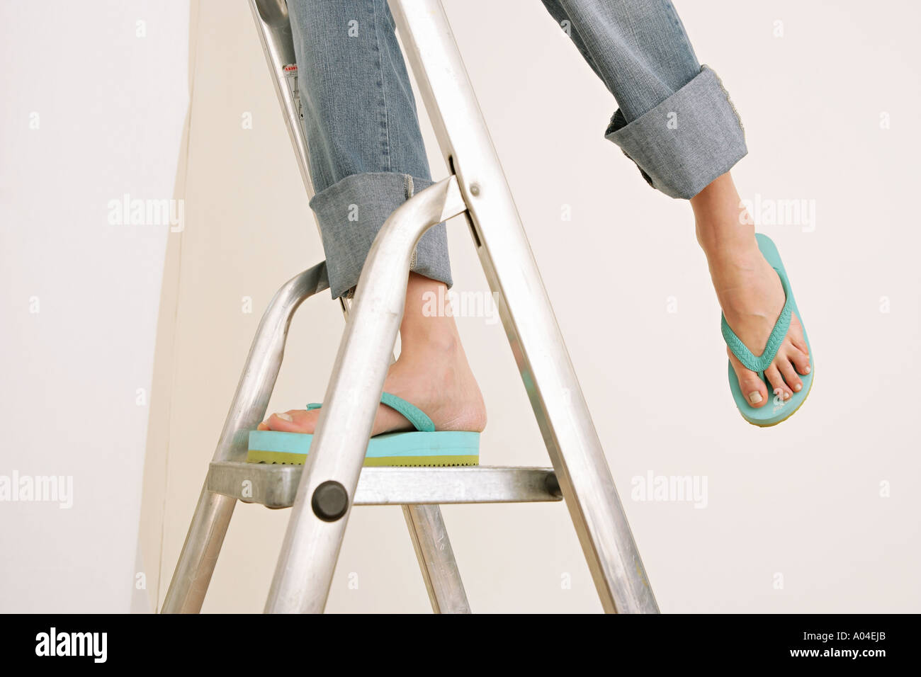 close up of female feet in flip flops standing on stepladder Stock Photo