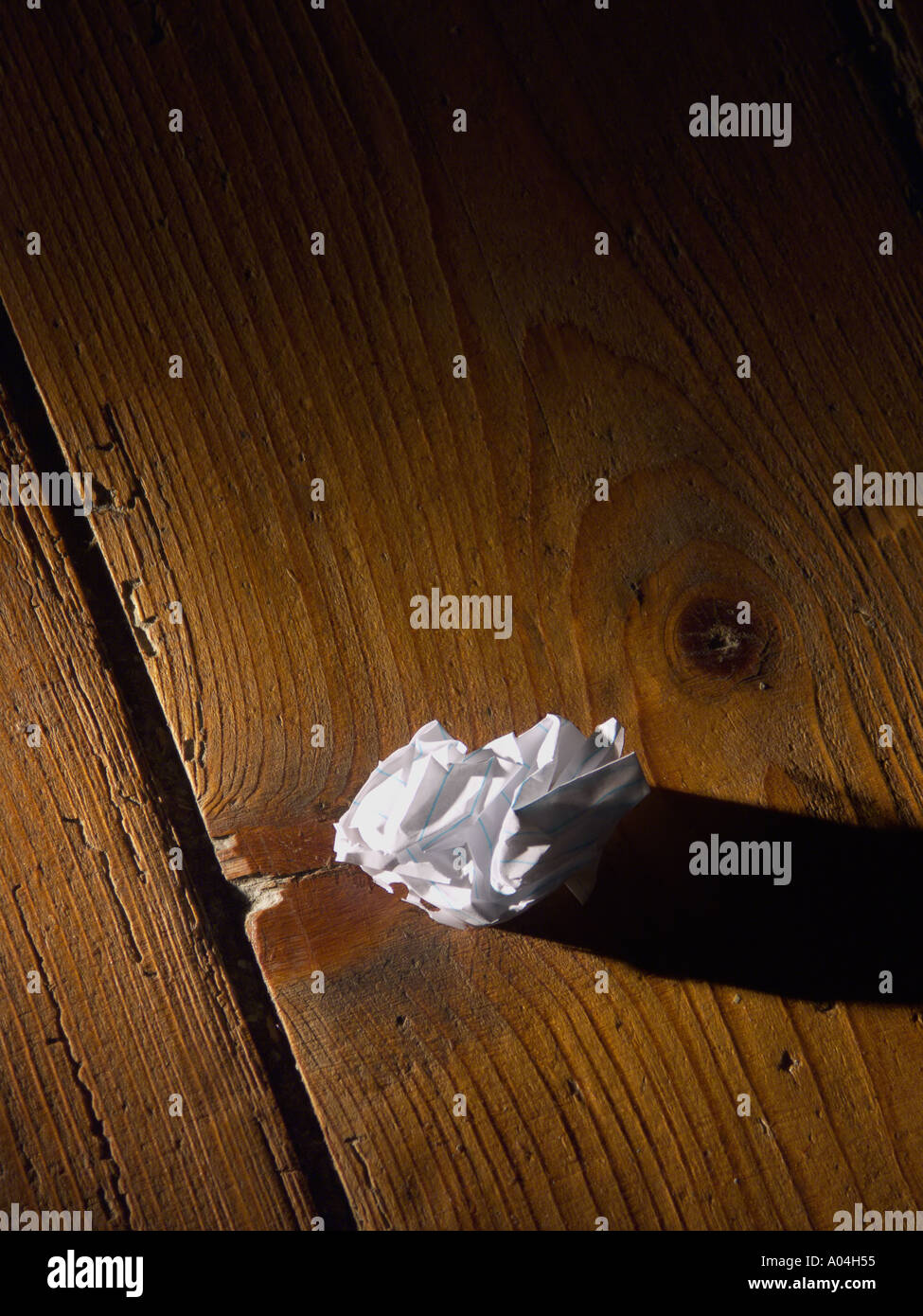 A screwed up ball of paper on the floor - Stock Image