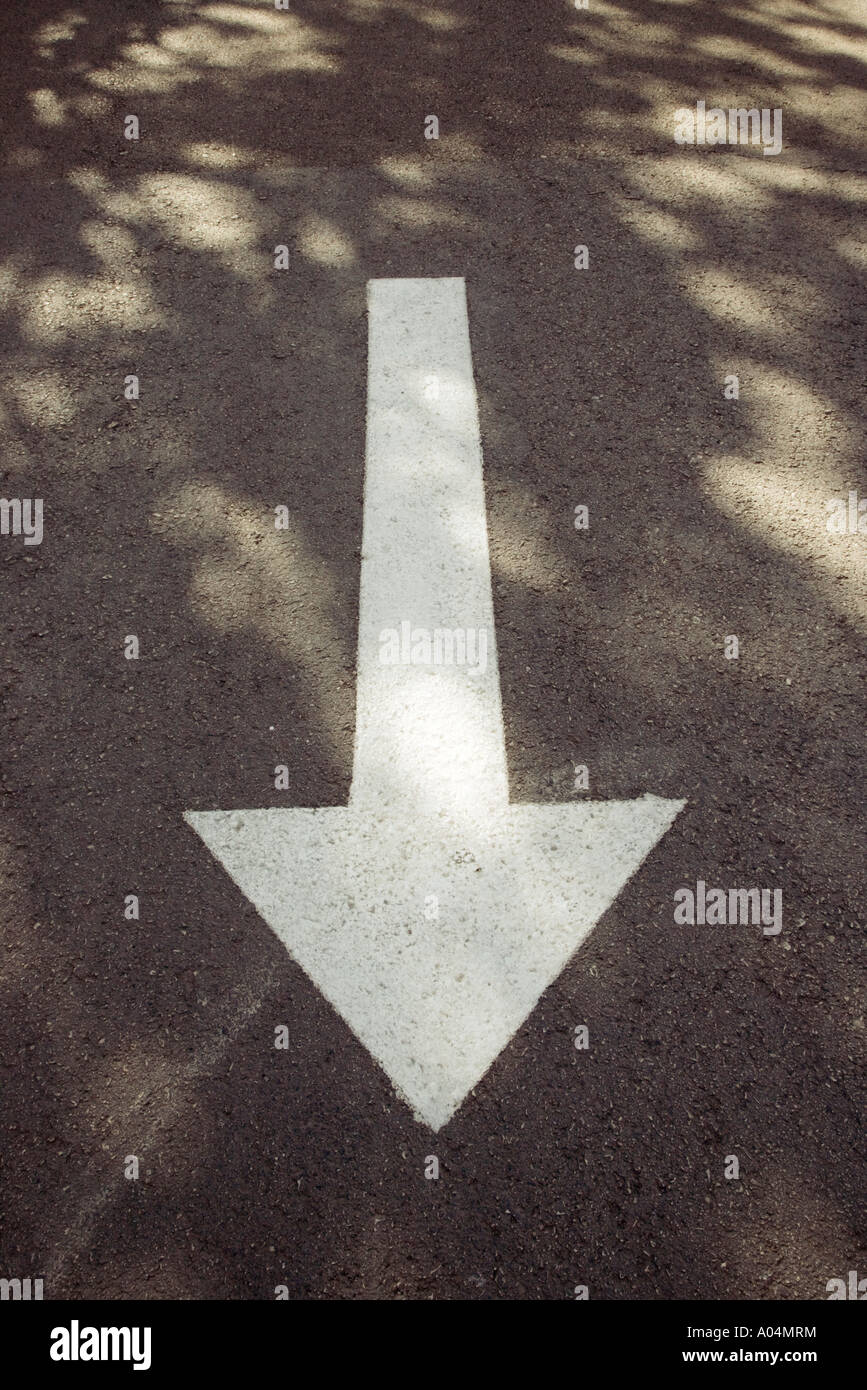 White arrow on road indicating direction for traffic to follow - Stock Image