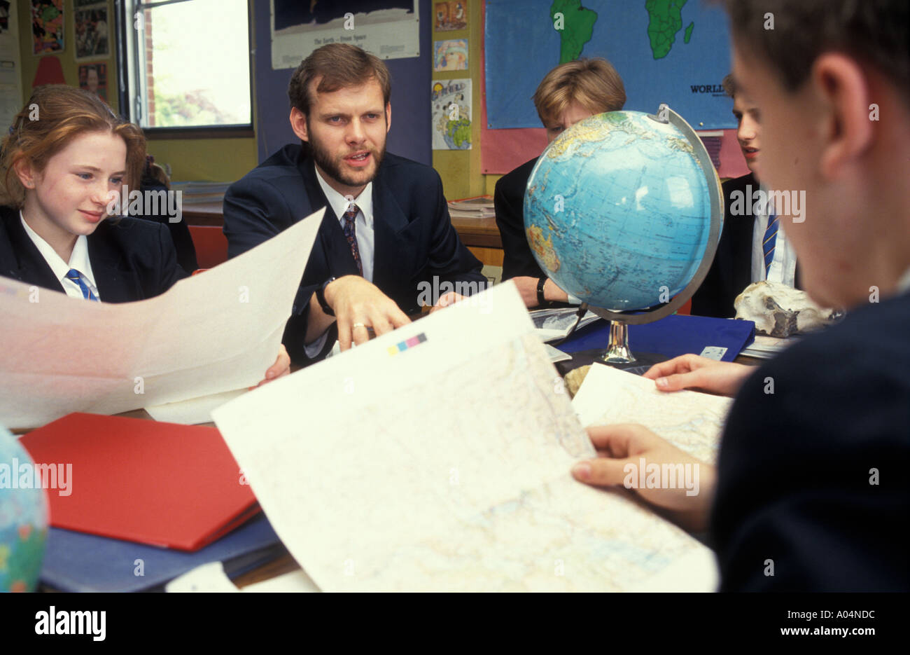 Secondary geography lesson with teacher showing students a world globe. - Stock Image