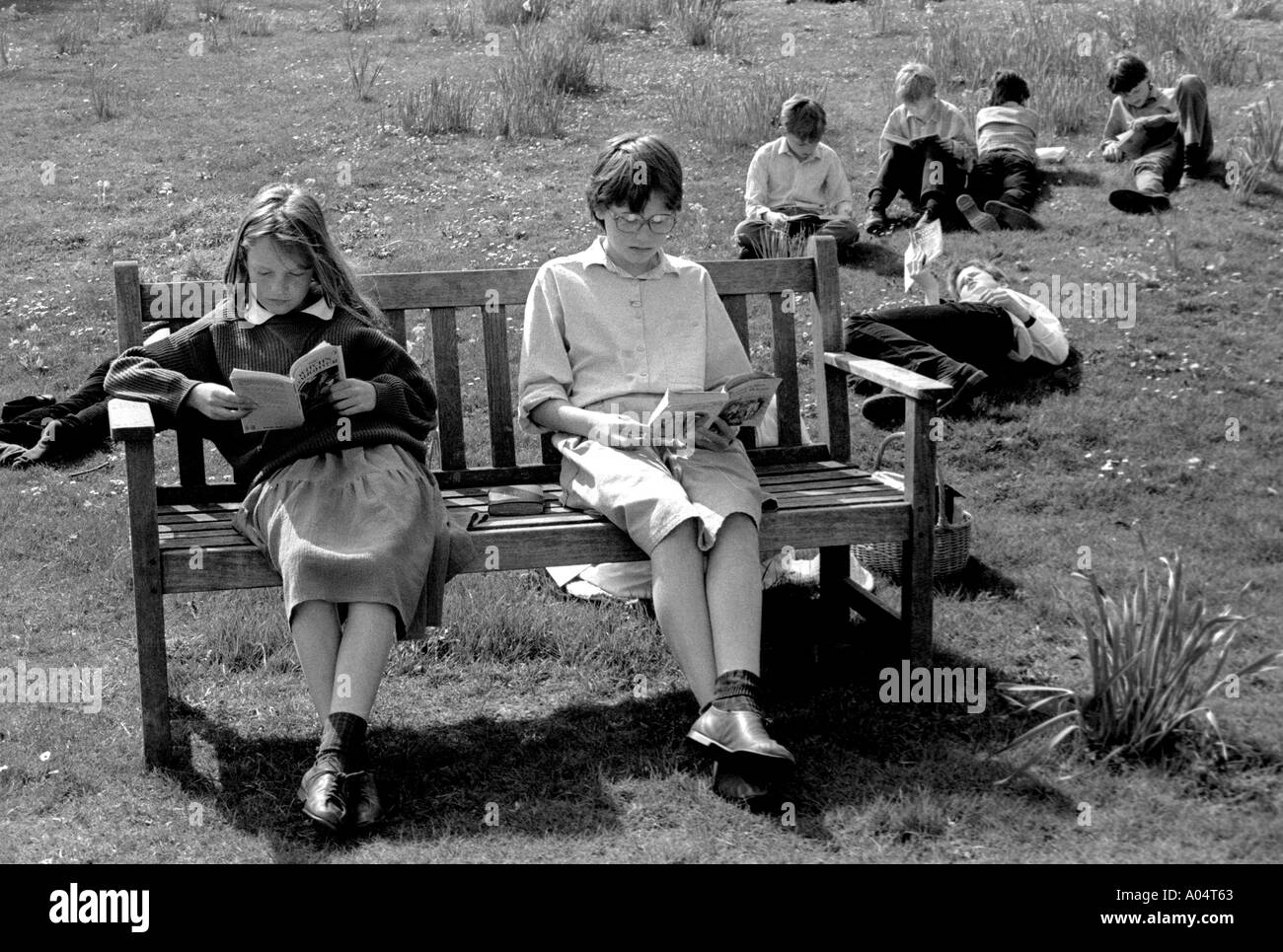 Kids doing their homework sitting on bench outdoors at private boarding school - Stock Image