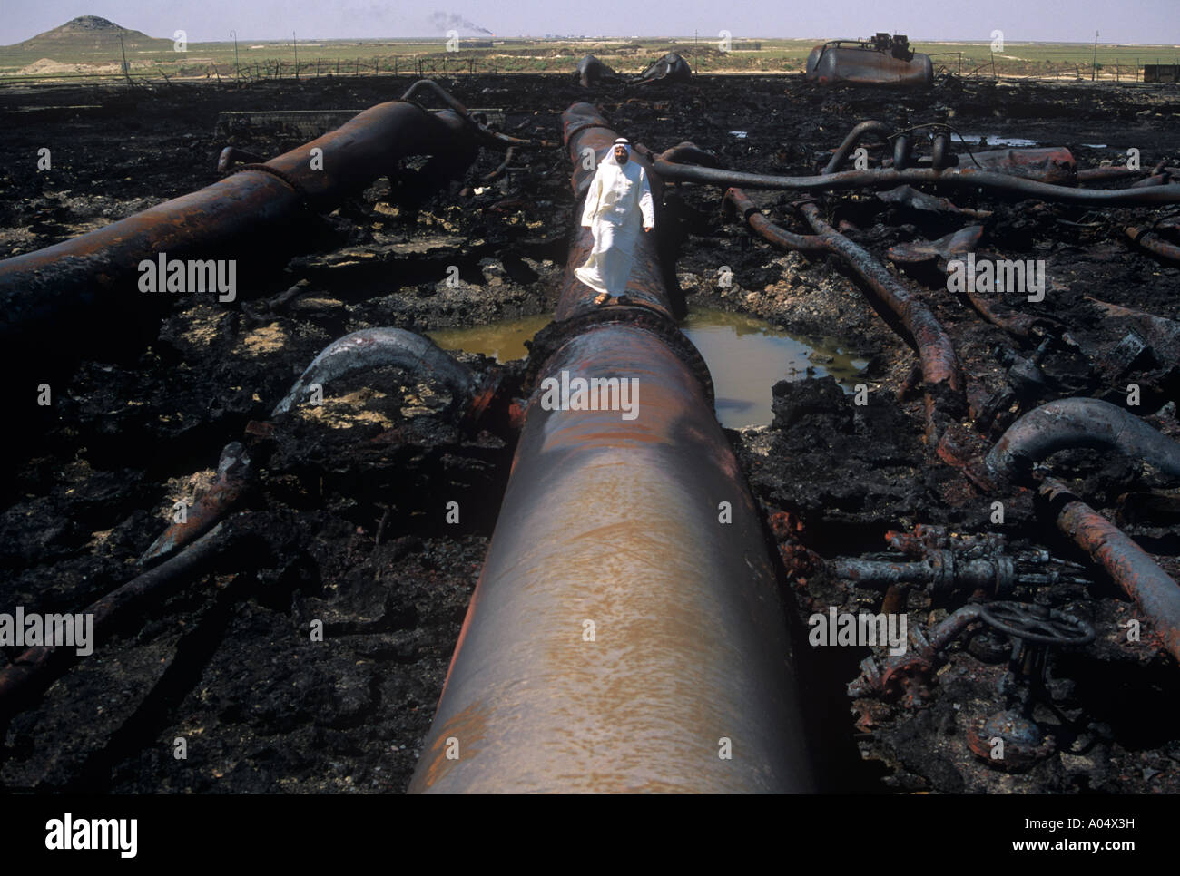 A Kuwaiti standing on oil pipelines bombed and burned by Iraq during the first Gulf War - Stock Image