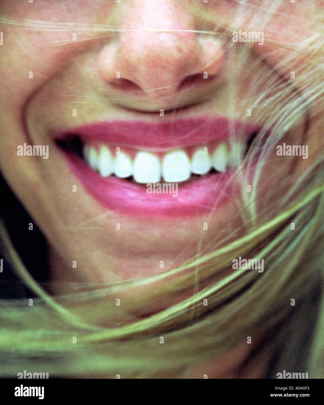A close-up of a woman smiling with the wind blowing and showing her teeth. - Stock Image