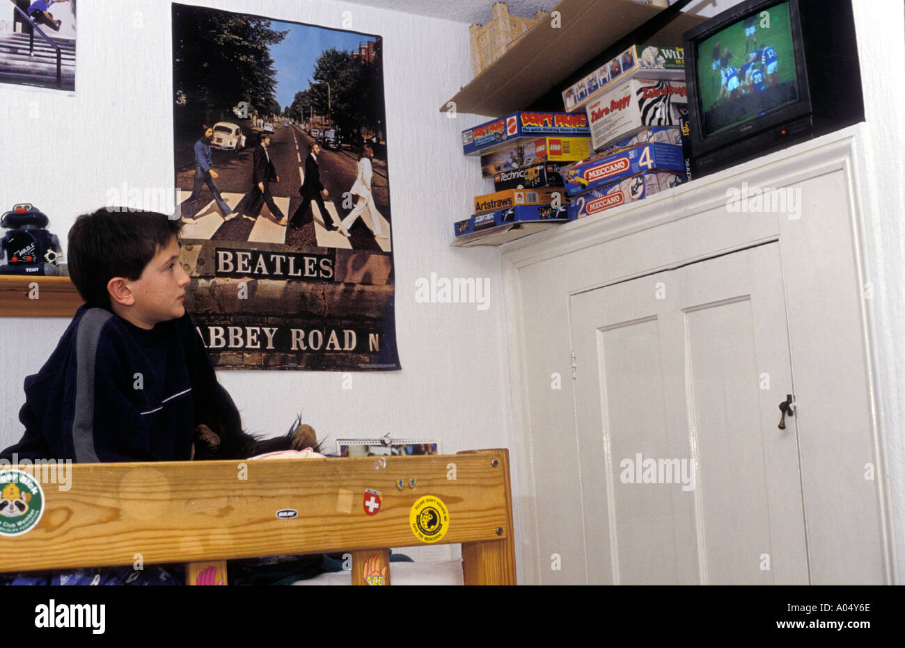Young Boy Sitting On Top Of Bunk Bed Watching Football On Television
