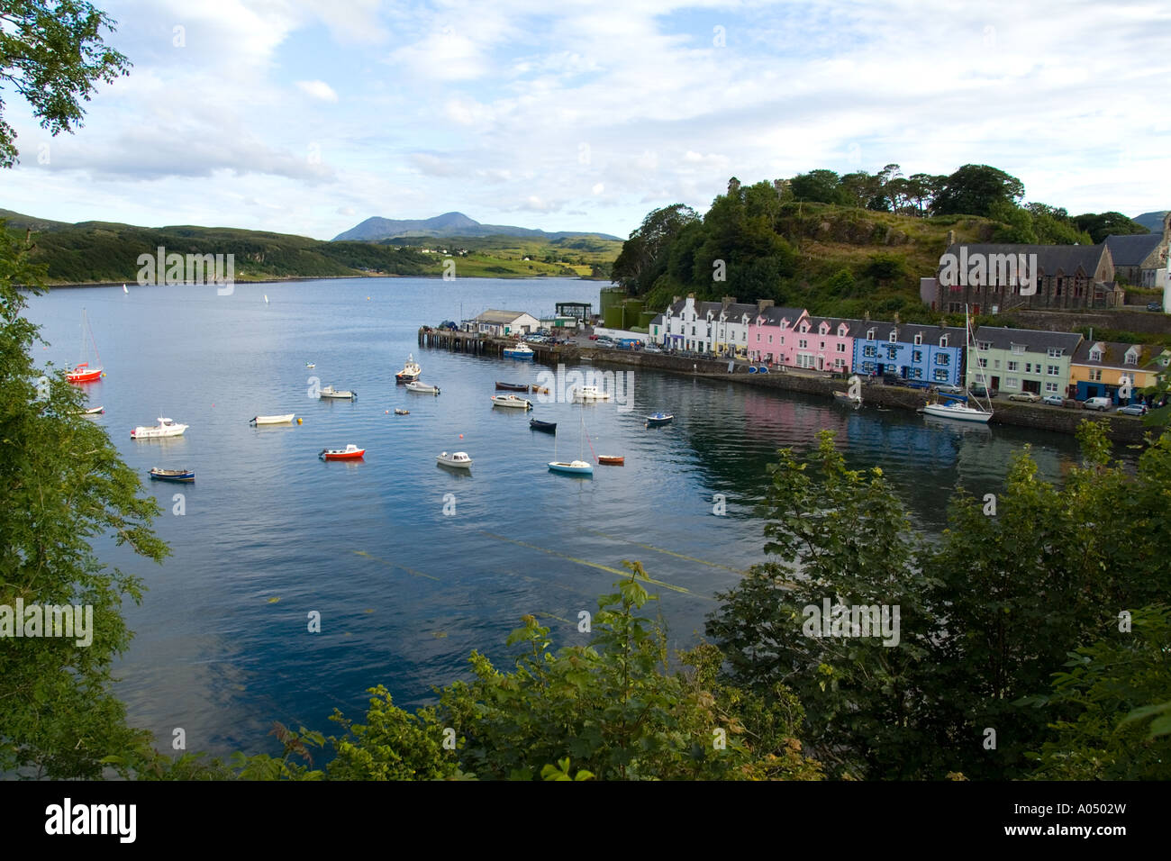 Beautiful port and sailboats with reflections in small tourist village of Portree in Isle of Skye Western Highlands Scotland - Stock Image