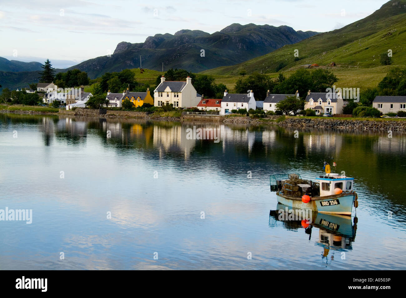 Beautiful photo of small village of Dornie with refections and boat in Western Highlands Scotlands - Stock Image