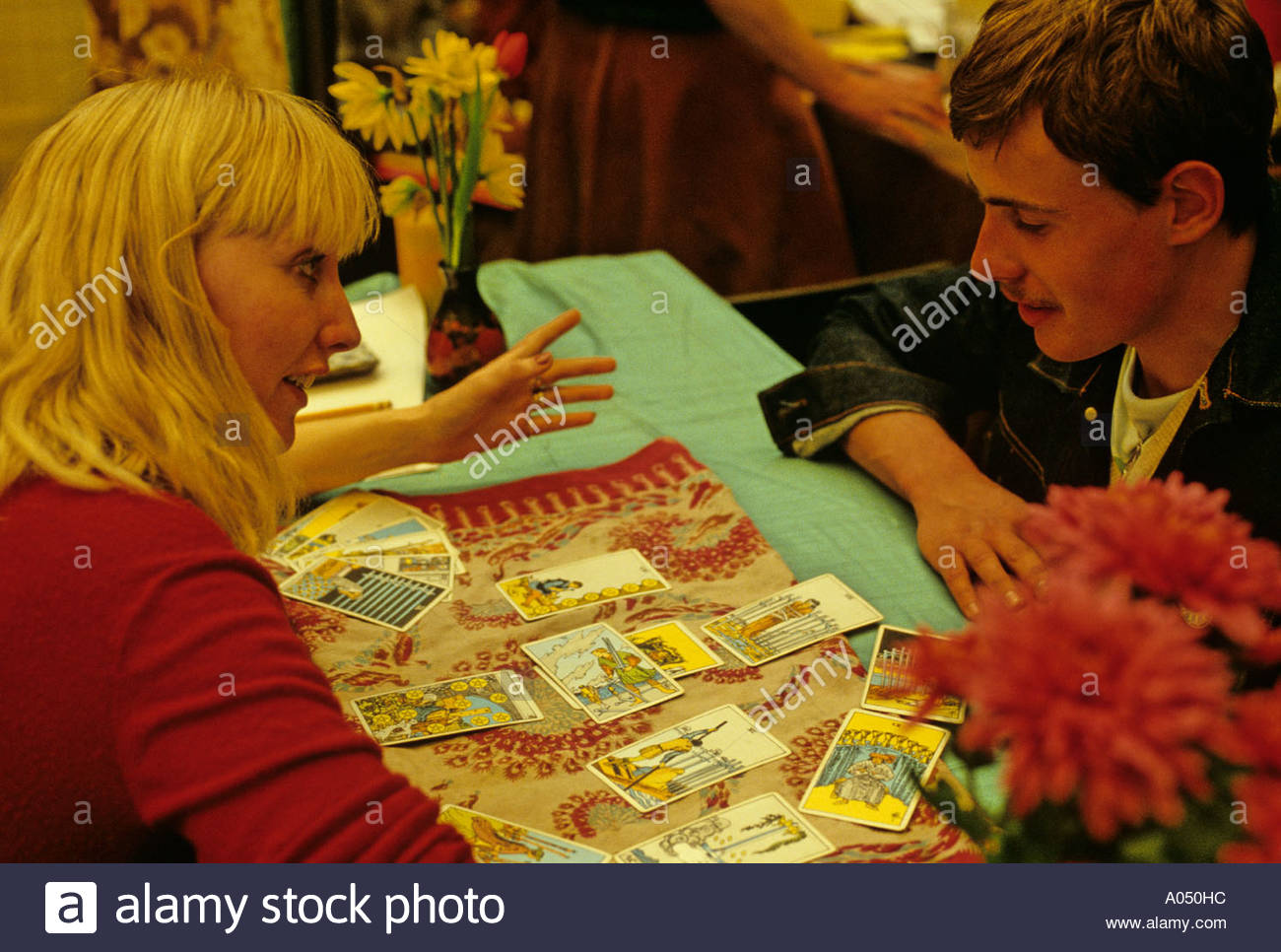 A young woman gives a fortune telling by reading Tarot Cards; London - Stock Image