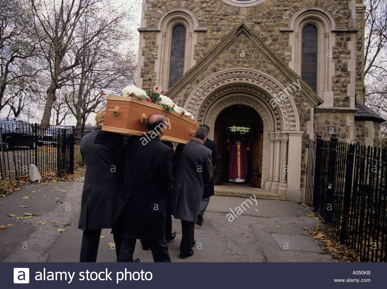 Pall bearers carrying a coffin into Old Saint Pancras church for a funeral; London - Stock Image