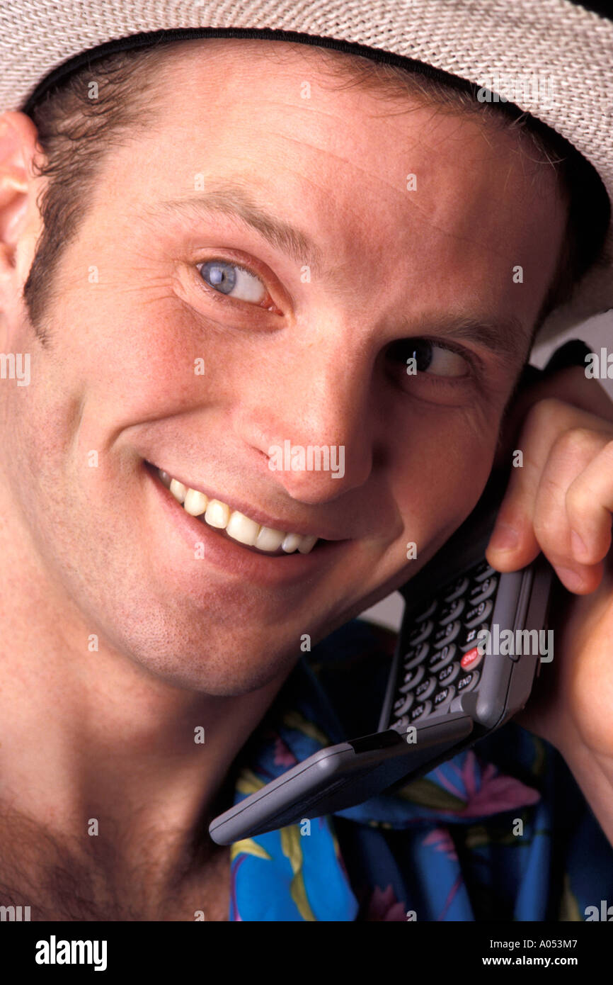 friendly man on holiday vacation talking on cell phone with excited happy relaxed expression on face getting good news - Stock Image