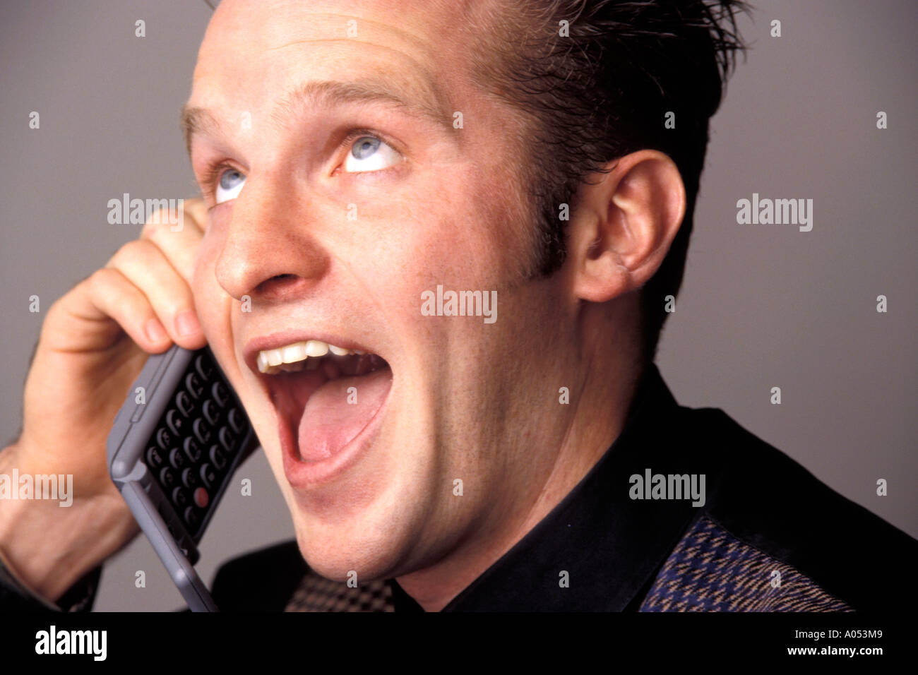 man having a conversation on the phone talking about exciting news that is shocking - Stock Image