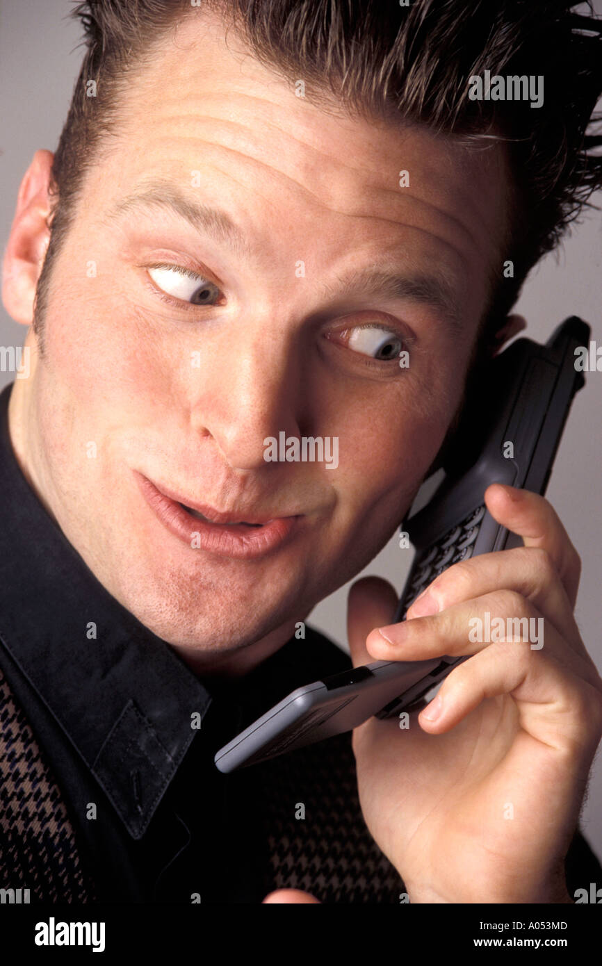 businessman talking on phone talking about fun exciting news making a funny face expression with a wow factor - Stock Image