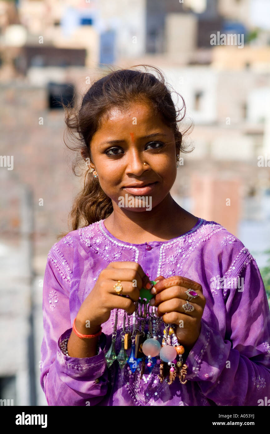 c367e9cf66 Beautiful portrait of young Indian girl aged 15 in purple in front of  village of Jodhpur in Rajasthan India