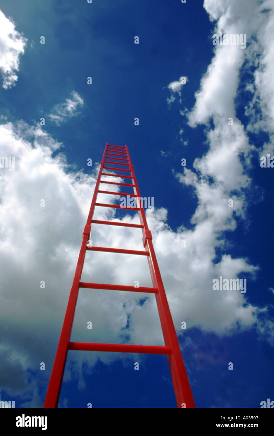 Red Ladder Rising Into Blue Sky And Clouds - Stock Image