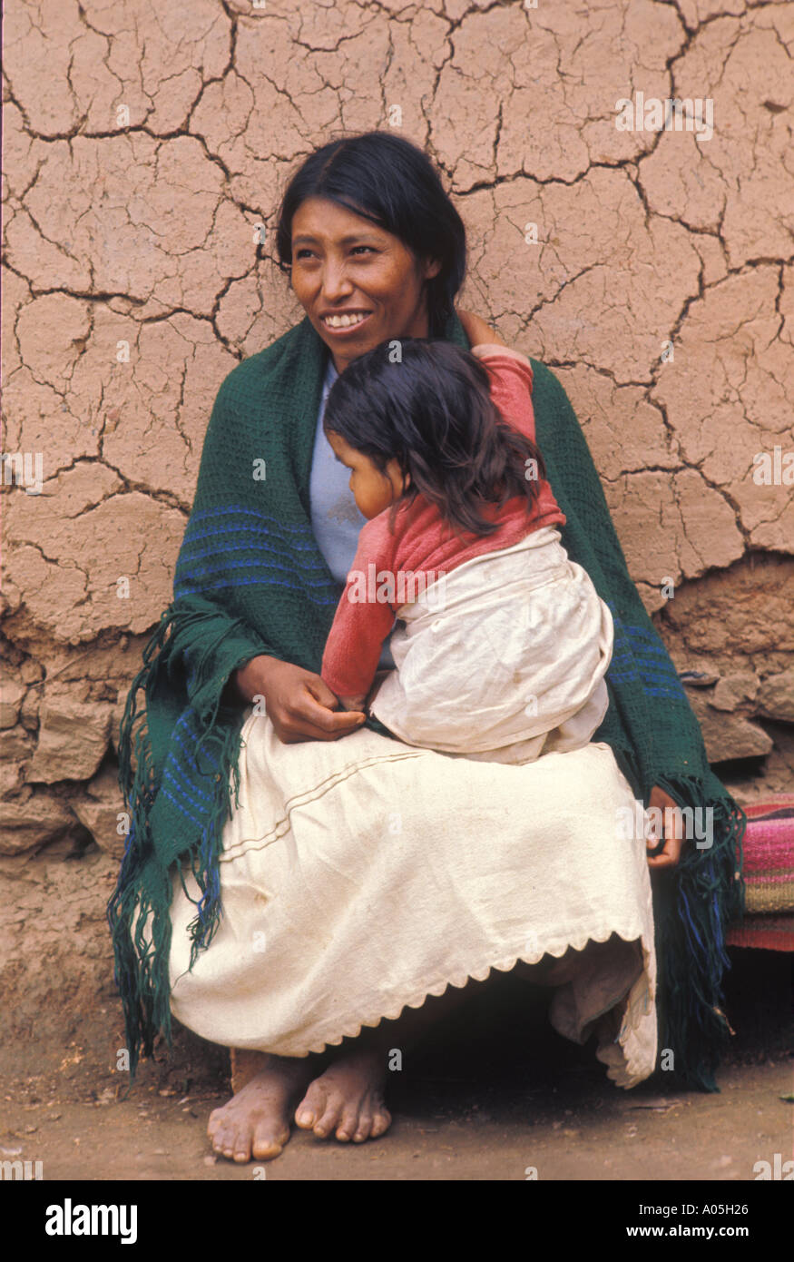 Bolivian Aymara Indian woman and baby sit beside a traditional mud wall on the Altiplano  Bolivia - Stock Image