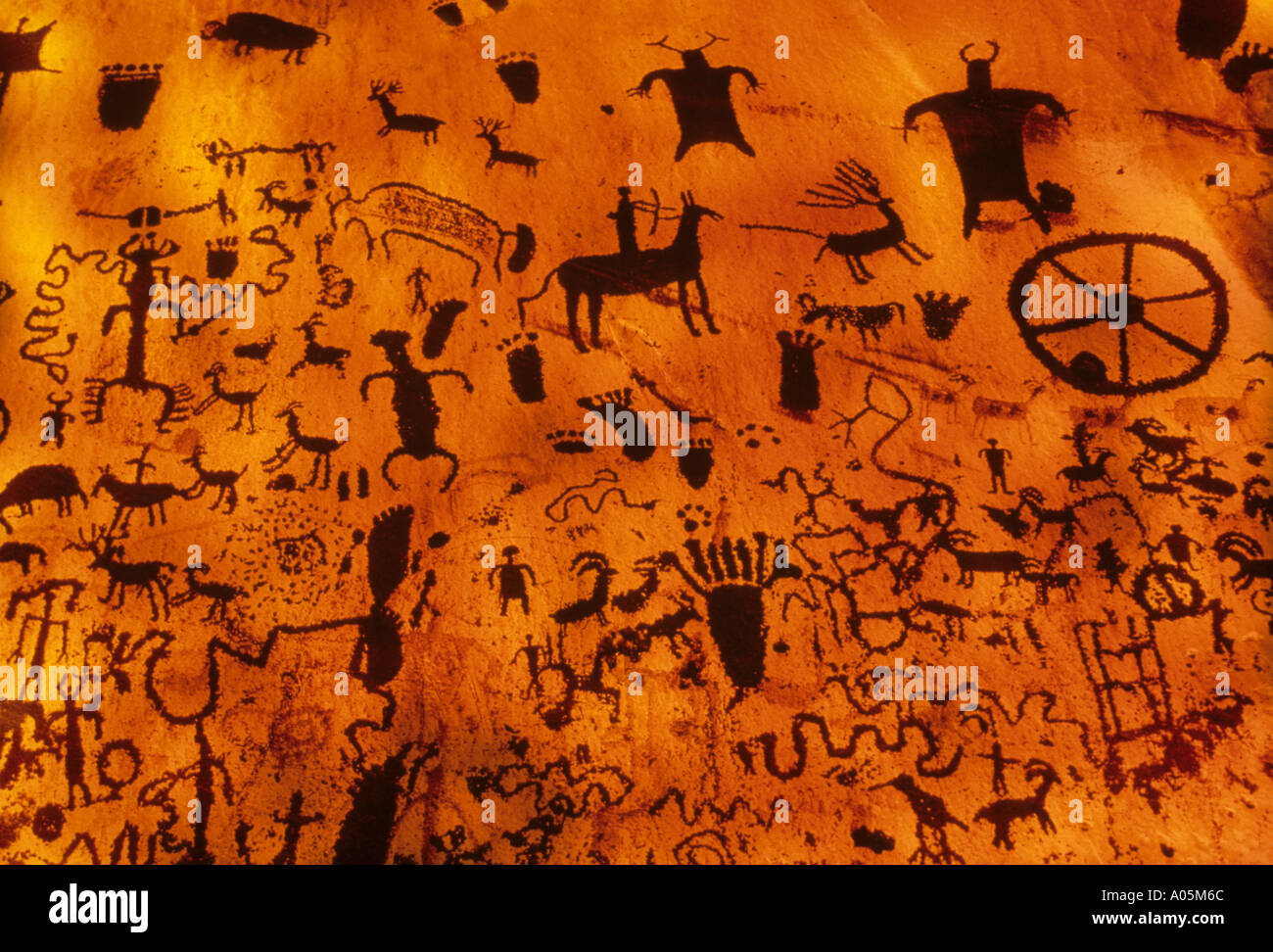 Variety of cave paintings and primitive art depicting people animals and a wheel - Stock Image