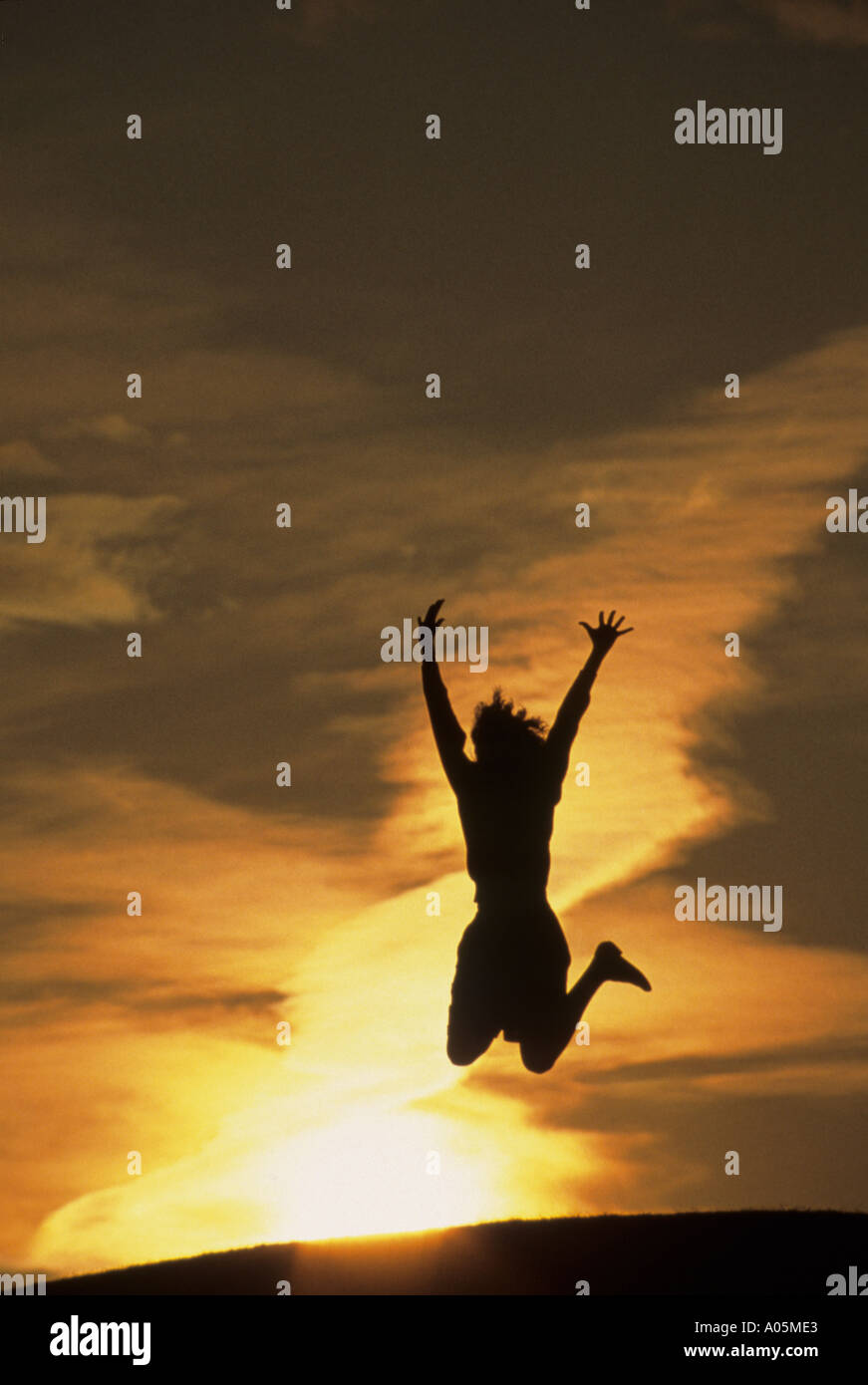 Silhouette of a woman jumping for joy with the sunset behind her Stock Photo