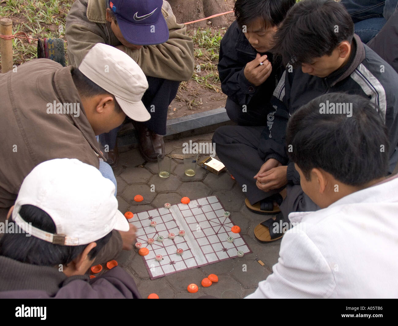 Vietnam Hanoi Centre Old Quarter culture pastimes men playing game of Co Tuong Chinese Chess in public park - Stock Image