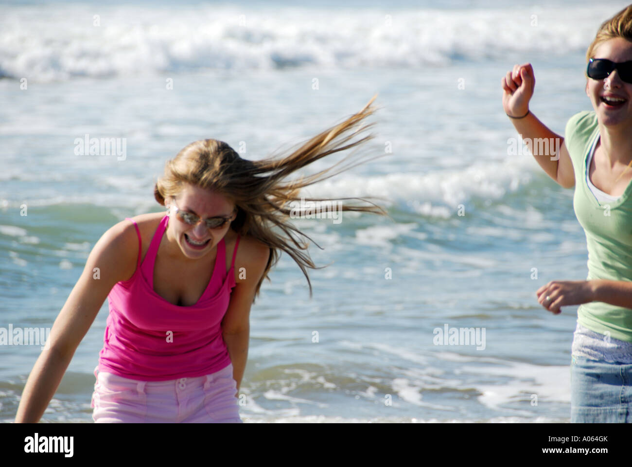 two teenage girls playing on beach together Stock Photo