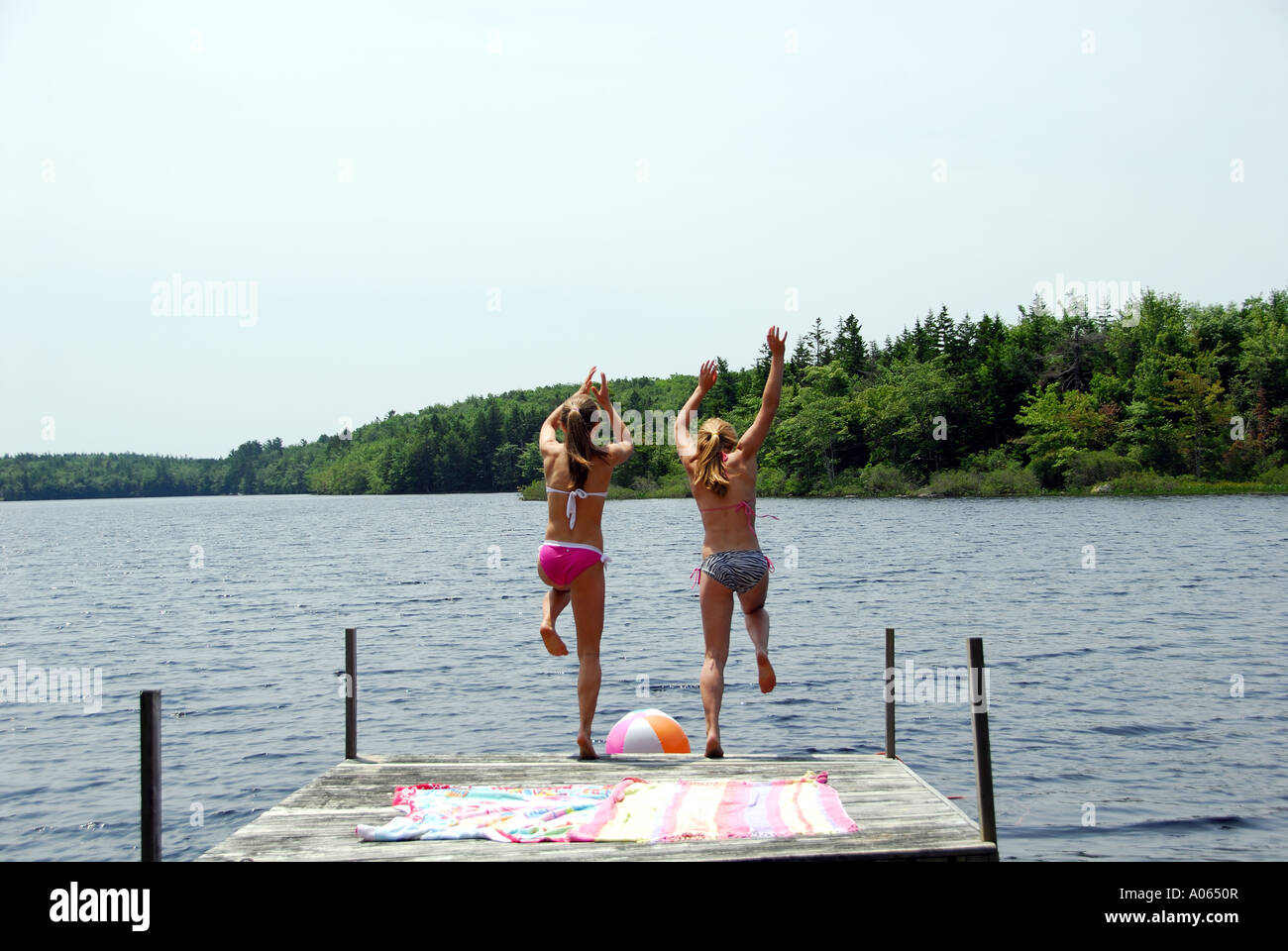 teenage girls jumping off dock into lake Stock Photo