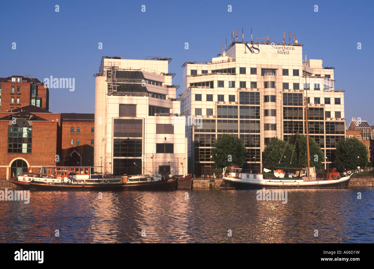 Quayside living: office buildings, apartments and live-aboard Dutch barges on Millwall Outer Dock, London Docklands, England - Stock Image