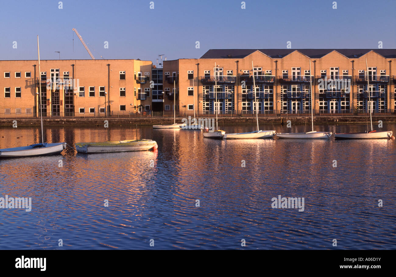 Modern quayside apartments overlooking sailboats on Millwall Outer Dock, London Docklands, England - Stock Image