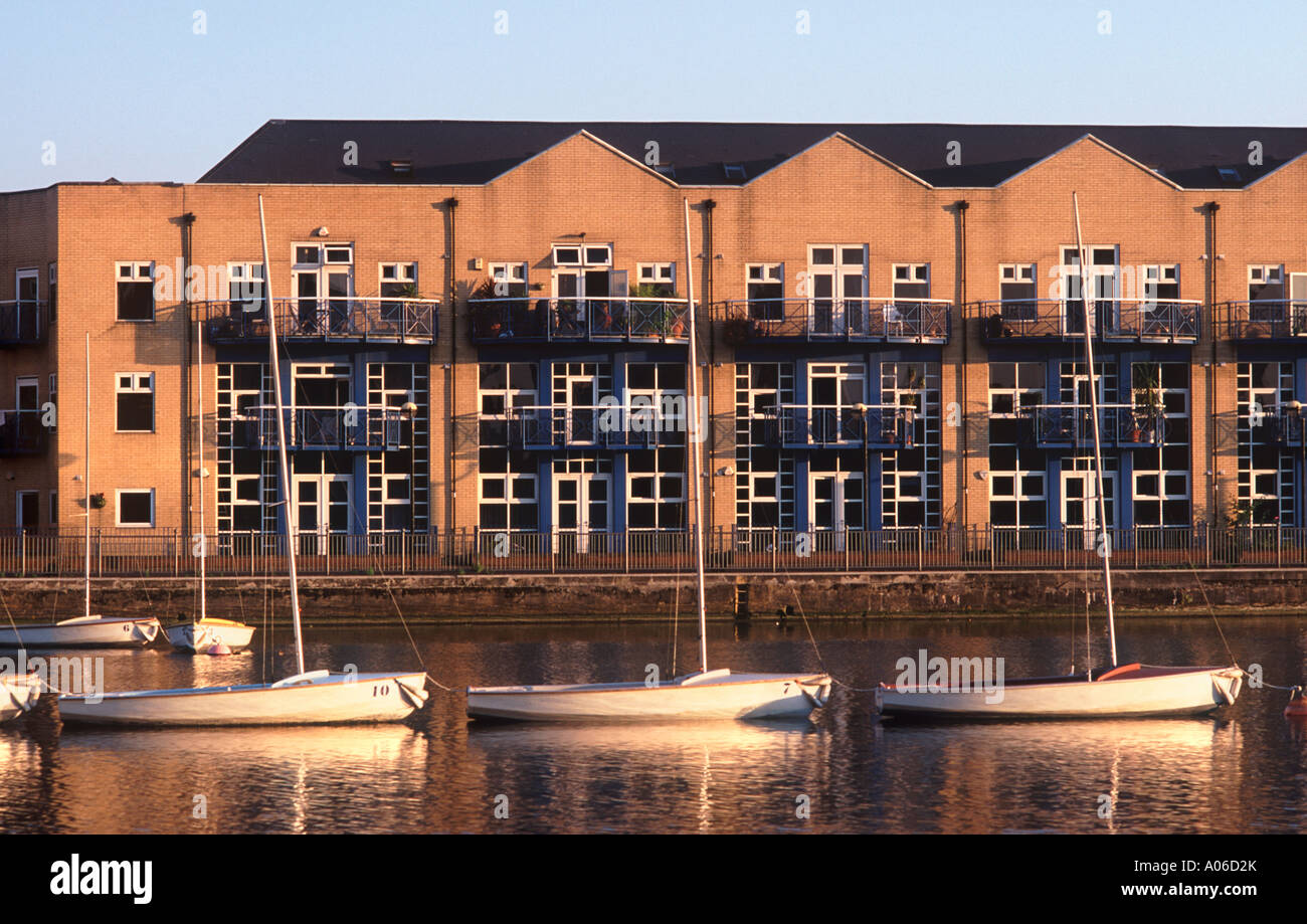 Modern quayside apartments overlooking three sailboats on Millwall Outer Dock, London Docklands, England - Stock Image