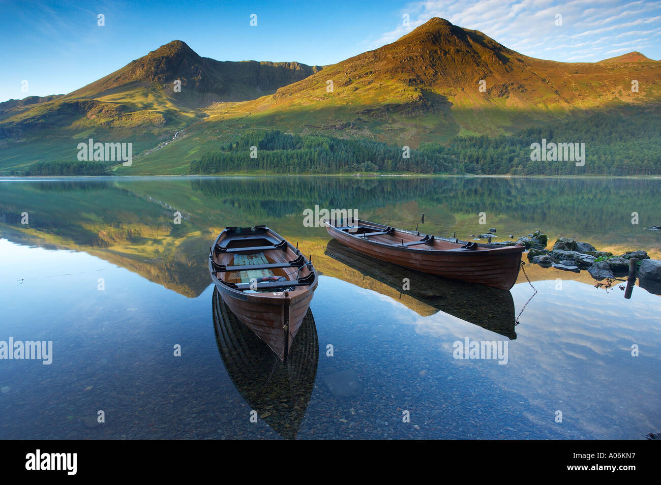 boats on the shore of Buttermere at dawn Cumbria Lakes District Cumbria England UK - Stock Image