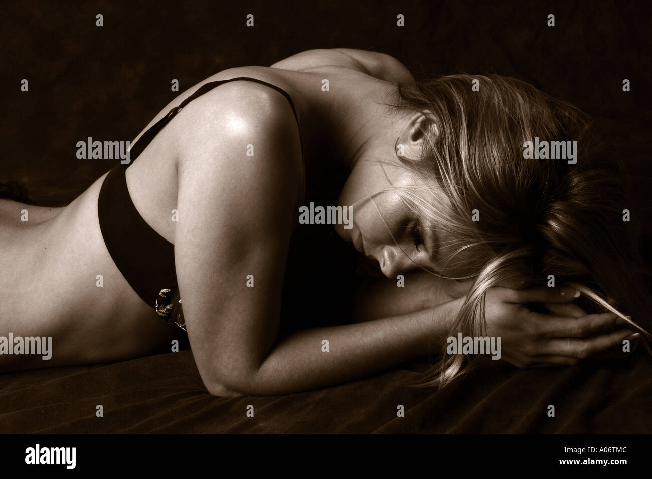 Girl Laying Face Down with Her Head on Her Hands - Stock Image