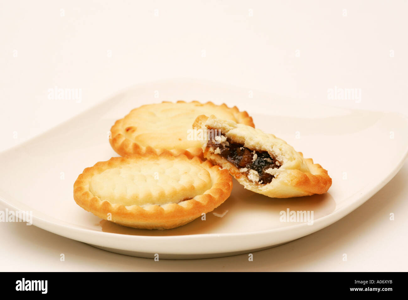 Half eaten mince pie on white plate with two 2 full pies traditional Xmas Christmas snack food in England Britain UK & Half eaten mince pie on white plate with two 2 full pies ...