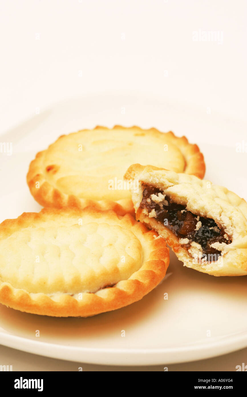 Closeup of a half eaten mince pie on white plate with two 2 full pies traditional Xmas Christmas snack food in Britain UK & Closeup of a half eaten mince pie on white plate with two 2 full ...